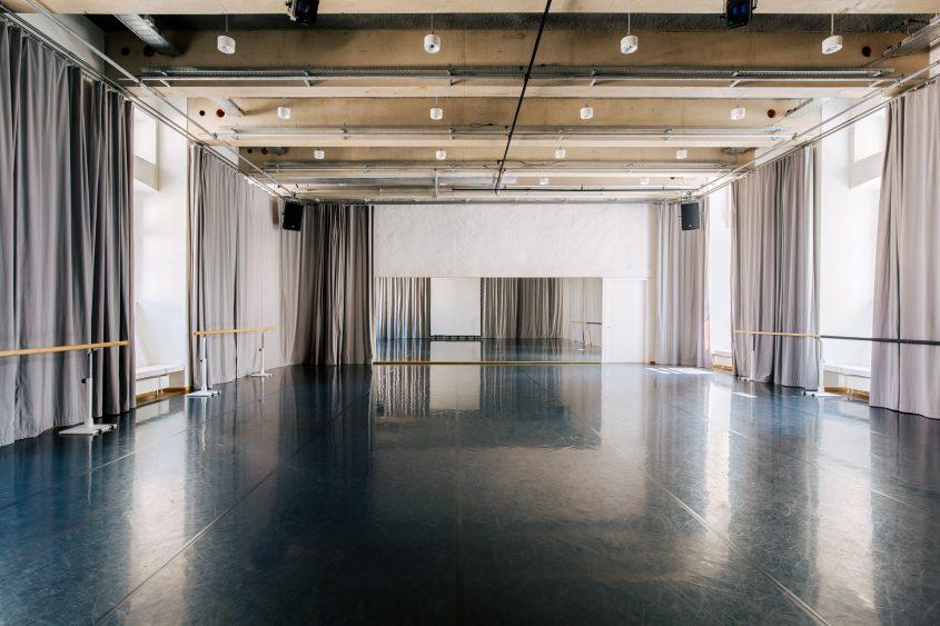 T Q W Studio 1, schwarzer Tanzboden, graue Vorhänge, Spiegel