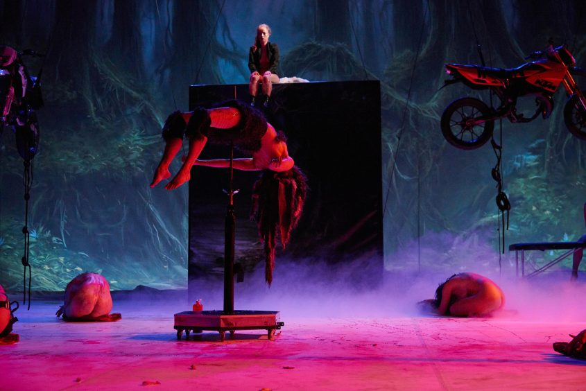 impaled half-naked woman in red light, two naked curled up bodies on the floor, woman sitting on black wall in the background, motorcycle hanging from the ceiling