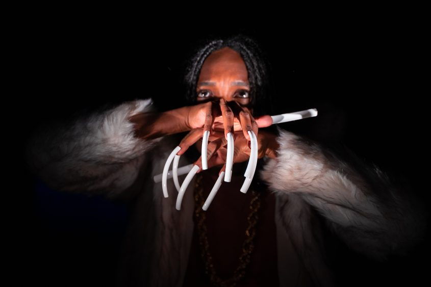 hands with claws crossed infront of the face, white fur jacket
