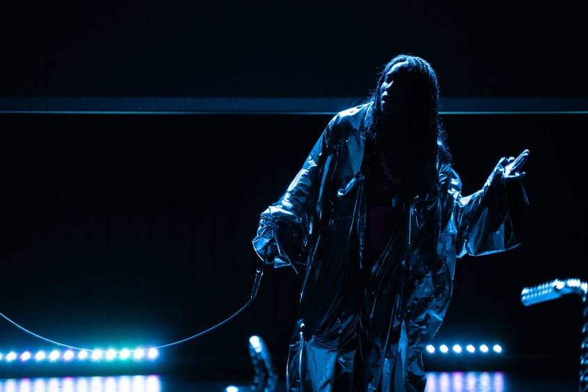 Cherish Menzo, Silvermantel und Schnur auf dunkler Bühne