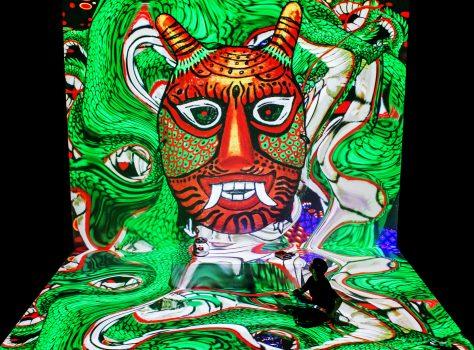 riesen Projektion rote Maske grüner Hintergrund, Jaha Koo sitzt als kleine Figur darin
