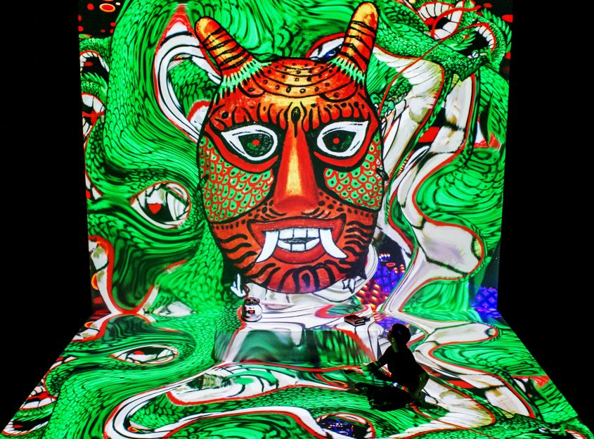 giant projection red mask green background, Jaha Koo is sitting in it as a small figure