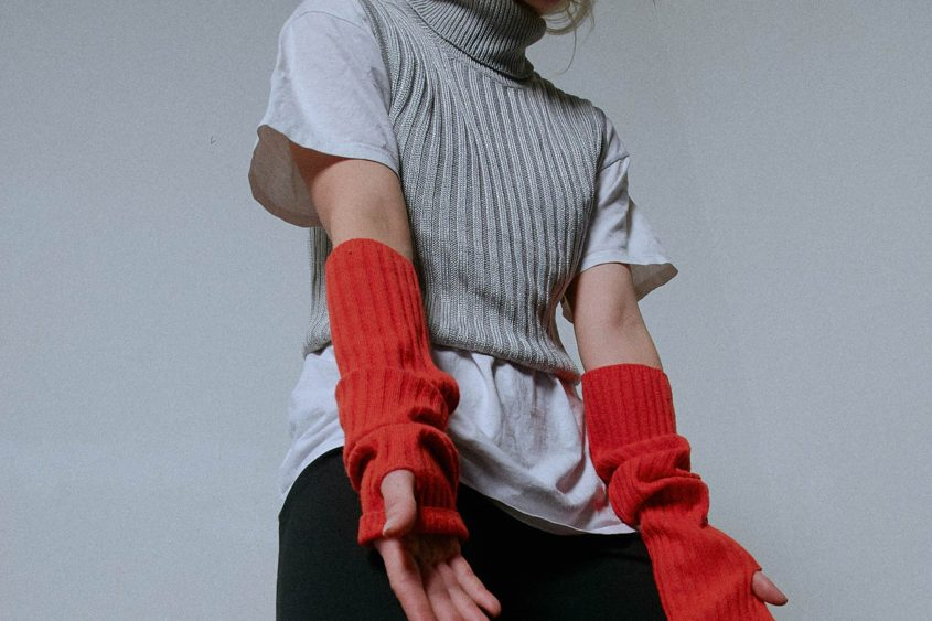 Image detail of upper body with T-shirt, knitted tank top and knitted wrist warmer