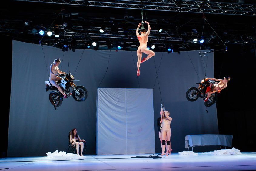 Performer on a chair, performers on two motorcycles hanging from the ceiling, performers hold a performer by rope winch by her hair in the air, all performers are naked