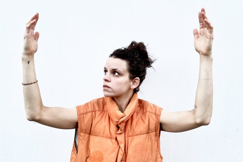 Karin Pauer in an orange vest, arms up, she looks to the right hand