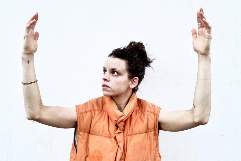 Karin Pauer in oranger Weste, Arme oben Blick zur rechten Hand