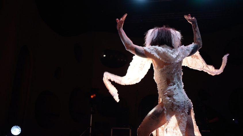 Jeremy Wade tanzt in weißem Paillettenkleid auf der Bühne, Rückenansicht