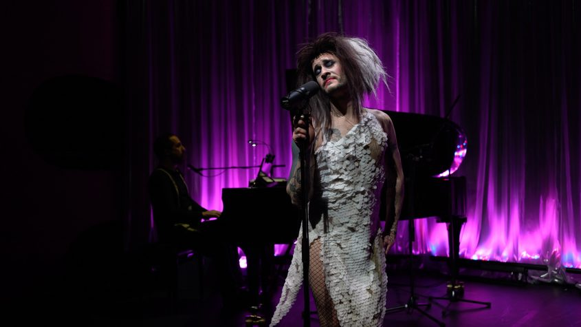 Jeremy Wade in a white sequin dress on stage, piano player in the background