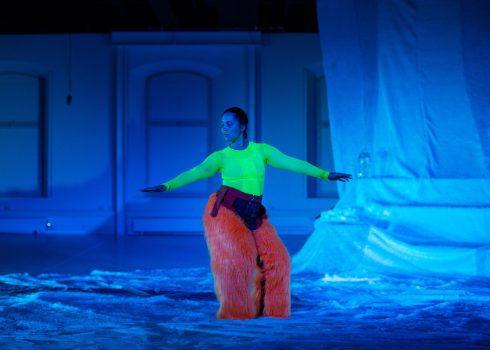 BamBam Frost in neongelbem Longsleeve und roter Fellhose in Blaulicht