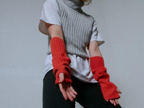 Ausschnitt Oberkörper mit T-Shirt, Strick Pullunder und Strick Handgelenkwärmer